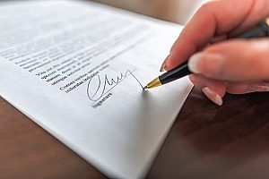 a man with a patented product signing a provisional application document to protect his products that have patents