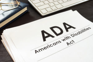 a stack of papers with the title ADA Americans with Disabilities Act next to a computer keyboard