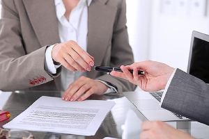 A Woman employee is taking pen for signing employment contract that has restrictive covenant on it