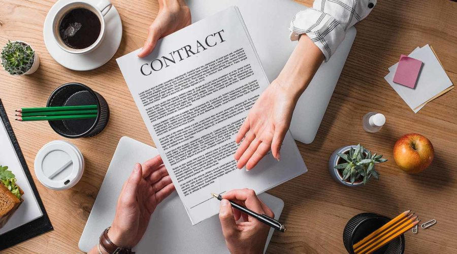 A person signing business contract. An Act of God clause can relieve parties from their contractual obligations