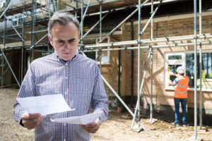 construction company boss experiencing hardship looks for a clause in the contract papers