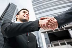 a business owner shaking hands with a contract law attorney
