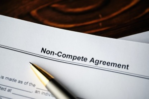 a non compete agreement contract on a table with a pen