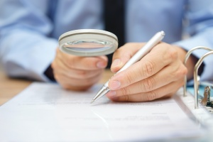 person doing their due diligence checklist with magnifying glass